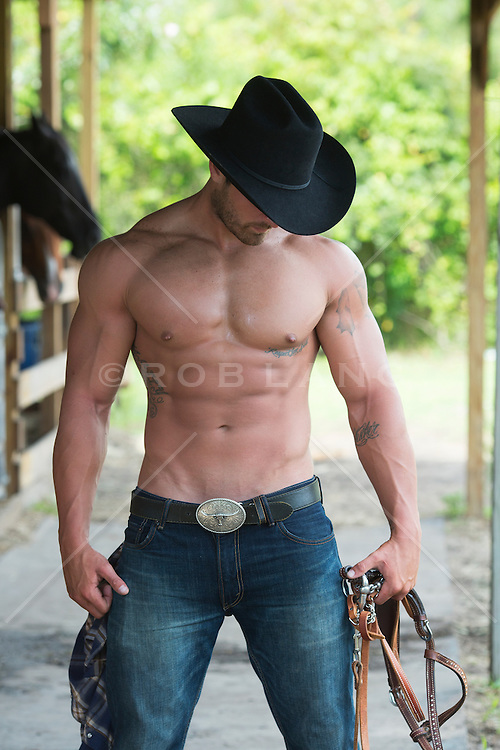 muscular cowboy without a shirt on a ranch