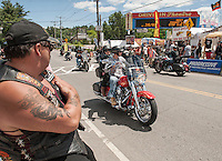 Frank Almeida of Fall River, MA watches a continuous flow of bikes parading through Weirs Beach on Friday afternoon.  (Karen Bobotas/for the Laconia Daily Sun)