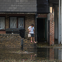 London, UK - 19 September 2014: a girl stands on a low brick wall as torrential rains cause floods and travel disruptions in East London