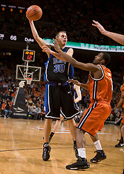Duke guard Jon Scheyer (30) passes over Virginia guard Jeff Jones (1).  The Virginia Cavaliers men's basketball team fell to the #6 Duke Blue Devils 86-70 at the University of Virginia's John Paul Jones Arena in Charlottesville, VA on March 5, 2008.