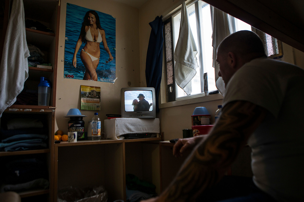 A prisoner sitting in his cell watching Kojak on the TV. HMP/YOI Portland, Dorset, United Kingdom.