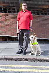 Vision impaired man with his guide dog standing by the edge of a road,