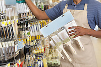 Midsection of male store clerk holding painting tools