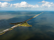 Nederland, Noord-Holland, Gemeente Wieringen, 16-04-2012; Den Oever, begin Afsluitdijk, gezien naar het noordoosten. Aan de horizon is de kust van Friesland zichtbaar. De 32 kilometer lange dijk vormt de waterkering tussen Waddenzee (links) en IJsselmeer (rechts). In de dijk de Stevinsluizen (spuisluizen of uitwateringssluizen). Het 'eiland' heet Robbenplaat. Aanleg van de dijk vormde onderdeel Zuiderzeewerken, initiatief van ingenieur Cornelis Lely..Den Oever, beginning Enclosure Dam, looking east. Frisian coast at the horizon (32 kilometers away). The dike forms the barrier between the Wadden Sea (left) and IJsselmeer lake (right). The Stevin sluices sluice surplus water to the Wadden sea. Construction of the dam was part of the Zuiderzee Works, an initiative of engineer Cornelis Lely..luchtfoto (toeslag), aerial photo (additional fee required).foto/photo Siebe Swart.luchtfoto (toeslag), aerial photo (additional fee required).foto/photo Siebe Swart