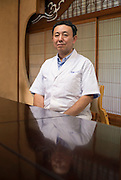 Hiroshi Ishikawa, who runs Hokushu Kurabu, poses for  photo at his restaurant Odate, Akita Prefecture Japan. The restaurant has served the dish for well over a century. Photographer: Rob Gilhooly