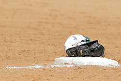 17 April 2016:  Baseball cap sitting on a baseball mitt containing the baseball on top of 1st base between innings with a pair of sunglasses during an NCAA division 3 College Conference of Illinois and Wisconsin (CCIW) Pay in Baseball game during the Conference Championship series between the North Central Cardinals and the Illinois Wesleyan Titans at Jack Horenberger Stadium, Bloomington IL