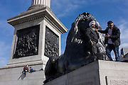 A Sikh man with another, beneath one of the four lions at the base of Nelson's Column in London's Trafalgar Square.