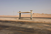 A remote bus shelter in a desolate desert landscape near Bagdad, Kharga Oasis, Western Desert, Egypt. The desert lies in the New Valley Governorate, 350 km (220 mi.) and measures approximately 80 km (50 mi) from east to west and 25 km (16 mi) from north to south and is patrolled by armed police convoys.