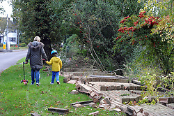 © Licensed to London News Pictures. 28/10/2013<br /> A Family walk past a fallen brickwall which fell in one piece on Chislehurst Road,Orpington,Greater London.<br /> Storm Damage today (28.10.2013)<br /> Photo credit :Grant Falvey/LNP