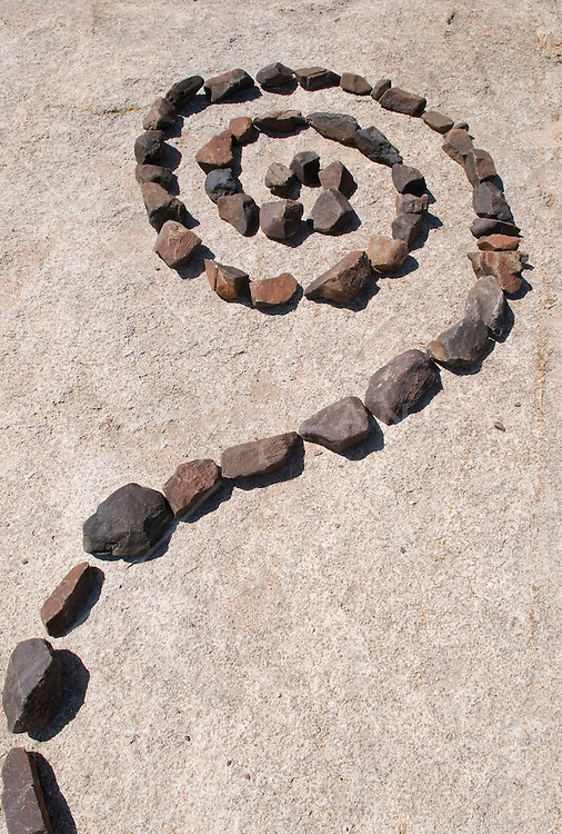 Curl made with small rocks placed on a larger rock