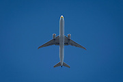 A Boeing 777-35R(ER) jet airliner with Jet Airways flies overhead in blue skies on its flight-path into London Heathrow airport, on 8th August 2018, in London, England.