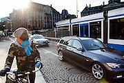 In Amsterdam staat een man met zijn fiets bij de Dam, waar auto's en een tram hem passerenn.<br /> <br /> In Amsterdam a man is waiting with his bicycle at the Dam, where cars and a tram are passing by.
