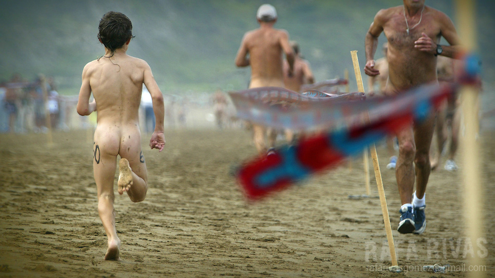 "A naked boy runs as he takes part in the ""Patxi Ros"" nudist cross-country race, 11 September 2004 on the beach of the northern Spanish Basque village of Sopelana. PHOTO RAFA RIVAS"