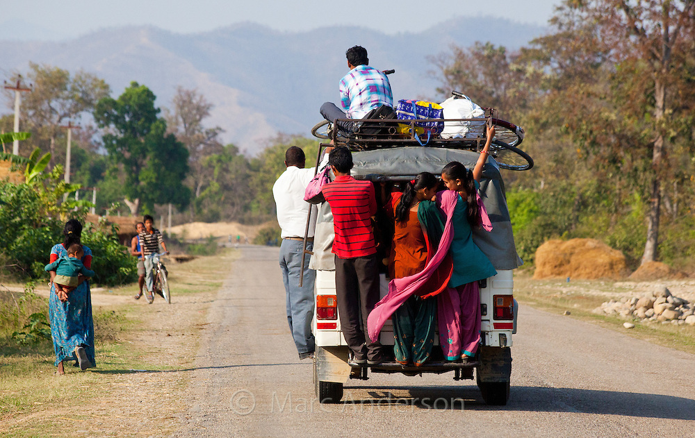 People standing on the back of a jeep bus, Bardiya, Nepal