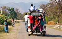 People standing on the back of a jeep bus, Bardiya, Nepal