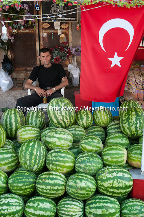 Bergama, Western Turkey, July 2011. A Turkish man sells watermelons from his stand under a historical buiding in Bergama. The Turkish Aegean coastline is littered with historical sites dating back to the Greek classical era. Photo by Frits Meyst/Adventure4ever.com.