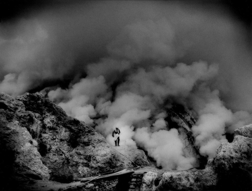 Collector of brimstone (sulphur) emerges with a heavy slab from the silent, noxious fumes inside the crater of Ijen Volcano. Java, Indonesia.  He lives for weeks at a time inside the sulphurous crater.