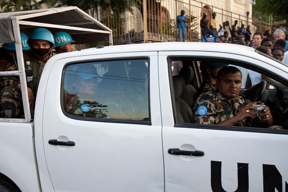 UN sodlers watch Michel Martelly supporters take to the streets marching and chanting after rumors of election fraud.