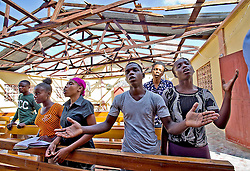 Jimmy Mondesir, middle, worships at L'Elise de Dieu in Morne la Source, Haiti, on October 9, 2016, without it's roof, lost in Hurricane Matthew. Photo by Patrick Farrell/Miami Herald/TNS/ABACAPRESS.COM
