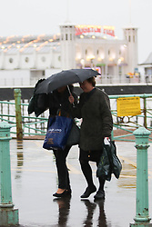 © Licensed to London News Pictures. 19/02/2015. Brighton, UK. Members of the public use their umbrella to shelter from the rain in Brighton. High winds and waves are battering the South Coast Photo credit : Hugo Michiels/LNP