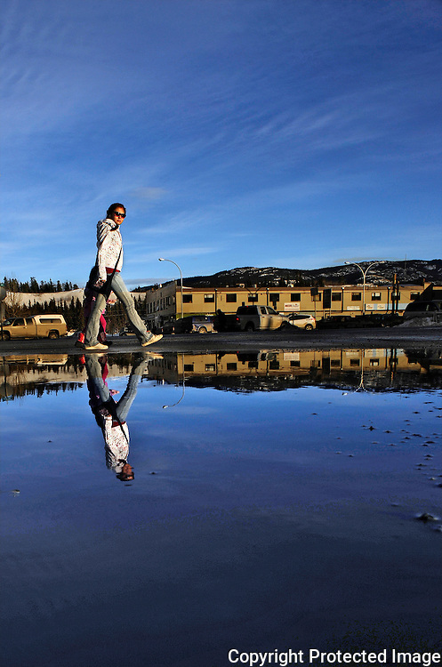 Ian Stewart/Yukon News<br /> A pedestrian is reflected in a street-wide puddle on Steele Street in downtown Whitehorse during a unusual warm spell in January 2014.