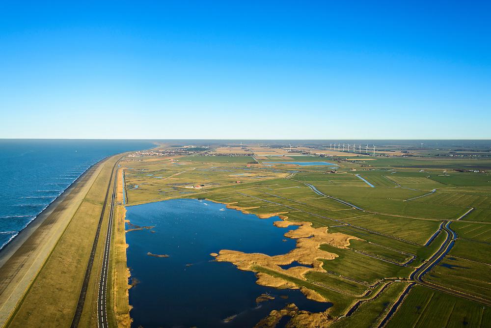 Nederland, Noord-Holland, Gemeente Schoorl, 11-12-2013; Camperduin, Hondsbossche en Pettemer Zeewering gezien naar het noorden, Petten en de duinen aan de horizon. Rechts van de zeedijk de Vereenigde Harger- en Pettemerpolder met 'De Putten' (ontstaan in het verleden door het uitgegraven grond om de  zeewering te verstevigen). De dijk is aangelegd als zeewering nadat de oorsrponkelijke duinen weggeslagen waren. Door erosie kalven de duinen langs de kust steeds verder af, de dijk steekt daardoor steeds meer uit in zee.<br /> Hondsbossche and Pettemer seawall seen to the north, Petten and the dunes on the horizon. Right side of the seawall and the United Harger Pettemer Polder with 'The Wells' (created in the past by using soil for strengthening the seawall). The dike was built as a seawall after the primal dunes were washed away. Because of erosion the dunes decrease in size, therefore the sewall sticks more and more out into the sea.<br /> luchtfoto (toeslag op standard tarieven);<br /> aerial photo (additional fee required);<br /> copyright foto/photo Siebe Swart