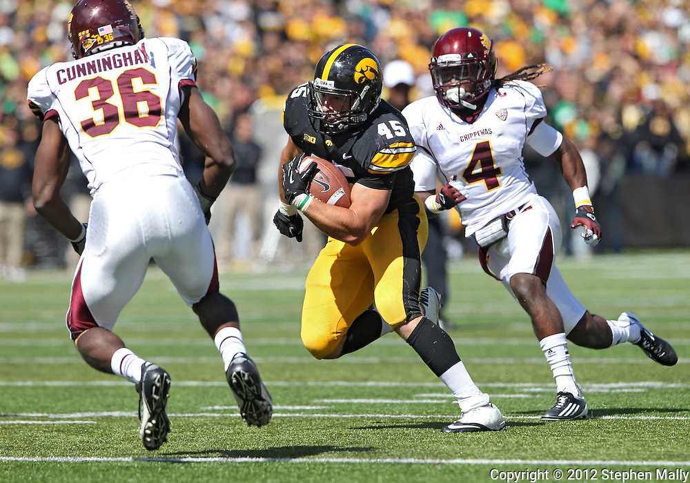 September 22 2012: Iowa Hawkeyes fullback Mark Weisman (45) tries to avoid Central Michigan Chippewas defensive back Avery Cunningham (36) and defensive back Jahleel Addae (4) during the second half of the NCAA football game between the Central Michigan Chippewas and the Iowa Hawkeyes at Kinnick Stadium in Iowa City, Iowa on Saturday September 22, 2012. Central Michigan defeated Iowa 32-31.