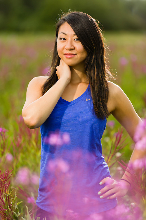 Woman in field of fireweed wildflowers on Joint Base Elmendorf Richardson at Six Mile Lake near Anchorage in Southcentral Alaska. Summer. Evening.