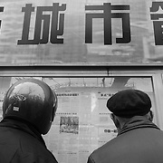 Two men reading the posted pages of the People's Daily newspaper, Nanjing Road, Huangpu District, Shanghai, China, Asia