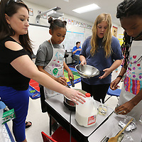 Rachel Davis, from left, keeps an eye on your yound chefs Taylor Norwood, 10, Emma Kate Smith, 11, and Jade Rucker, 10, as they make their sauce for chicken alfrado as part of a cooking camp held at Parkway Elementary School.
