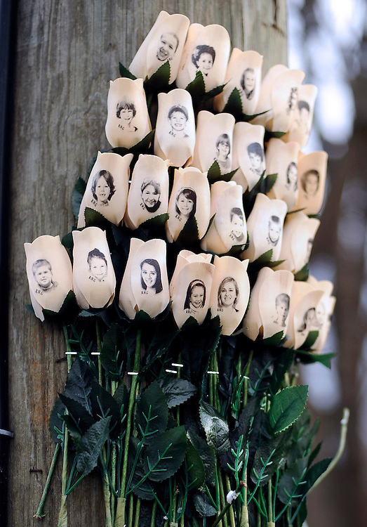 White roses with the faces of victims of the Sandy Hook Elementary School shooting are displayed on a telephone pole near the school on the one-month anniversary of the mass shooting that left 26 dead, including 20 children in Newtown, Conn., Monday, Jan. 14, 2013. (AP Photo/Jessica Hill