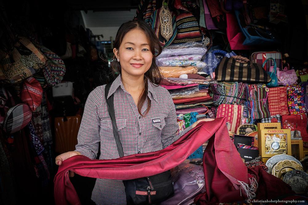 Eine Verkäuferin am Centrak Market in Phnom Penh verkauft Seidenschäle, eines der bei Touristen beliebtesten Souvenirs, da diese qualitativ hochwertig und günstig zu kaufen sind.