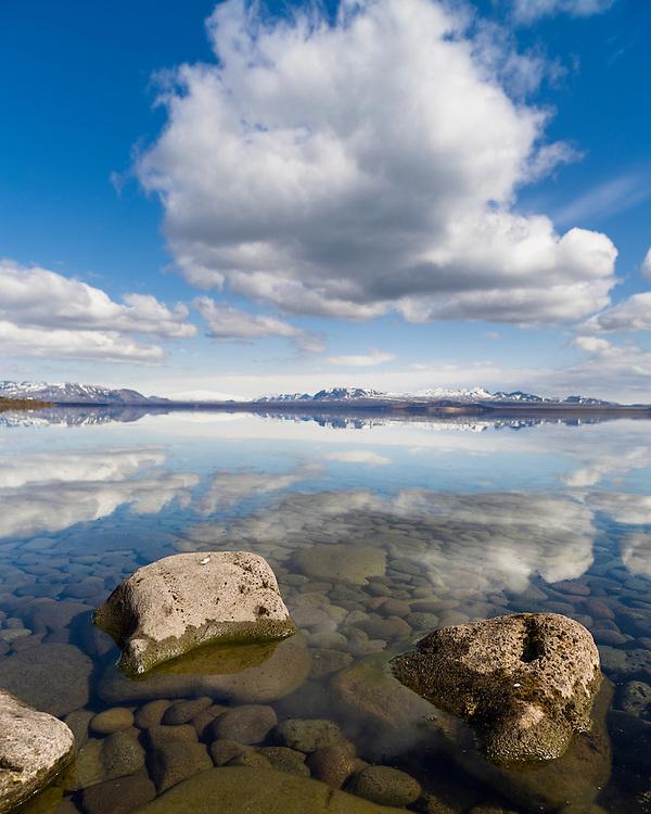 Lake Þingvellir reflects the sky above on a spring day.