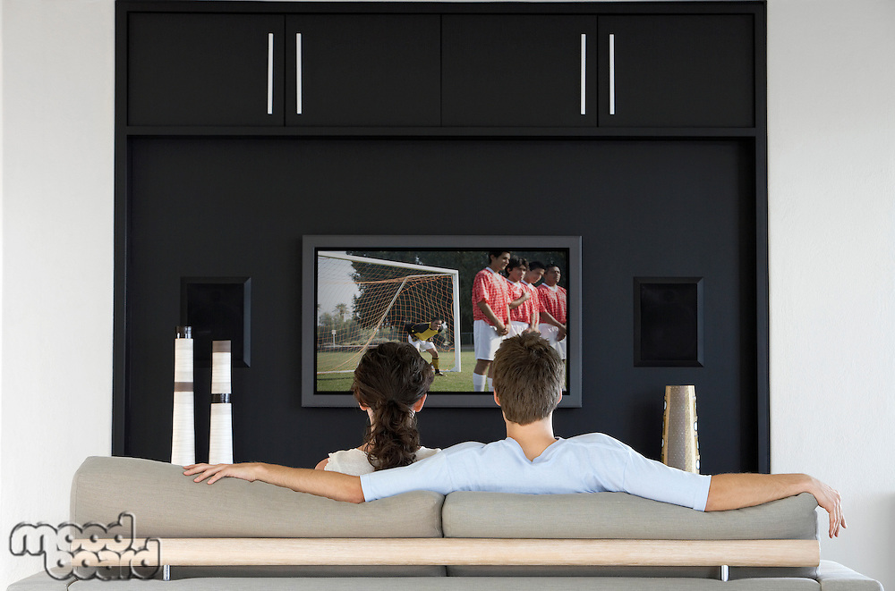 Back view of couple watching soccer game on television in living room