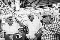 TAORMINA (ME) - 8 SETTEMBRE 2018: Anziani simpatizzanti della politica Lega e di Salvini in termini di immigrazioni, discutono di politica e migranti seduti in un bar a Taormina, l'epicentro dell'avanzata della Lega in Sicilia con il 23,52%, l'8 settembre 2018.