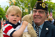Merrick, New York, U.S. - May 26, 2014 - GARRY GLICK, a member of American Legion Post 1282, holds his grandson MAX, almost 2, after the veteran marched in the Merrick Memorial Day Parade, which honored those who died in war while serving in the United States military.