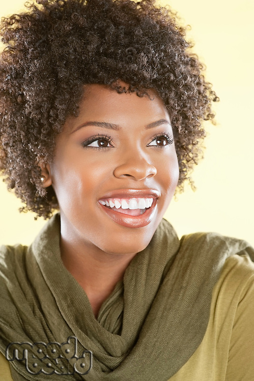 Cheerful African American woman looking away over colored background