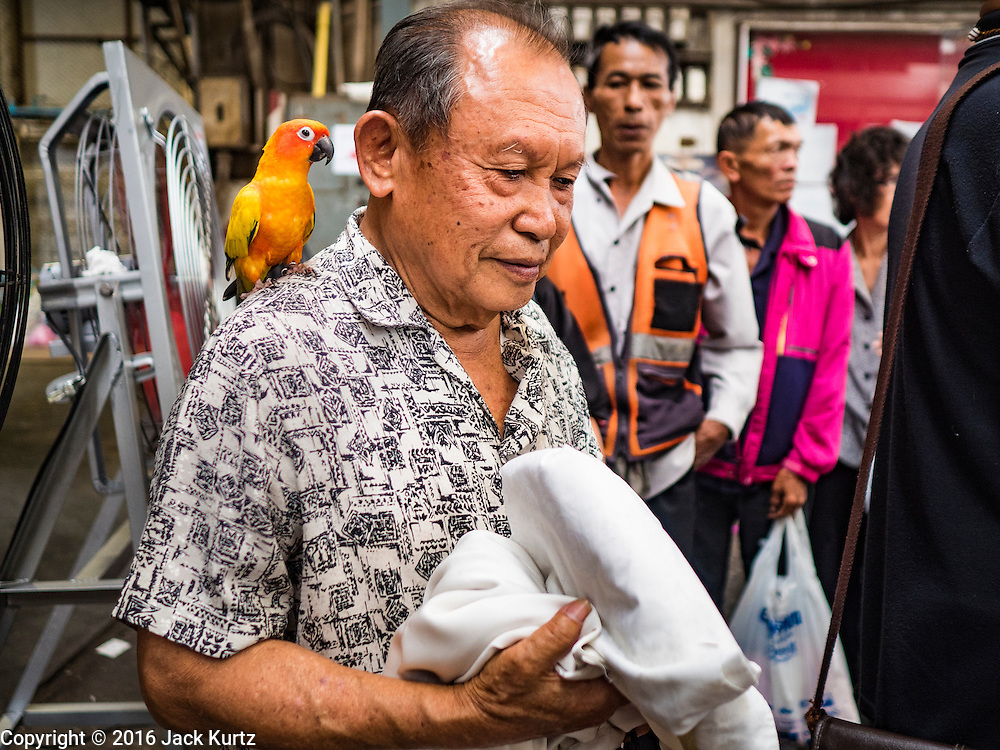 04 NOVEMBER 2016 - BANGKOK, THAILAND: A man with his pet parrot on his shoulder stands in line to drop off clothes to be dyed black at Krungthai Tractor. About 150 volunteers are working at Krungthai Tractor in Bangkok to dye clothes black for people in mourning following the death of Bhumibol Adulyadej, the King of Thailand. The government declared a one year mourning period, during which Thais are encouraged to wear black and a 30 day mourning period during which Thais are very strongly encouraged to wear black. Furthermore, black is mandatory for official mourning functions, including visits to the Grand Palace and Sanam Luang, the public ceremonial ground across the street from the Palace. The expectation to wear black created a shortage of black clothes in many markets and Thailand's poor couldn't afford what black clothes were still available. Community groups have started dyeing clothes for people who either can't find or can't afford black clothes. The clothes dyeing volunteers at Krungthai Tractor were organized by Thai actress Chompoo Araya A. Hargate and Thai fashion blogger Chavaporn Laohapongchana.      PHOTO BY JACK KURTZ