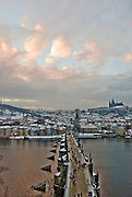 Prague, Czech Republic. Across the River Vitava on Charles Bridge with Prague Castle and the church at sunset.