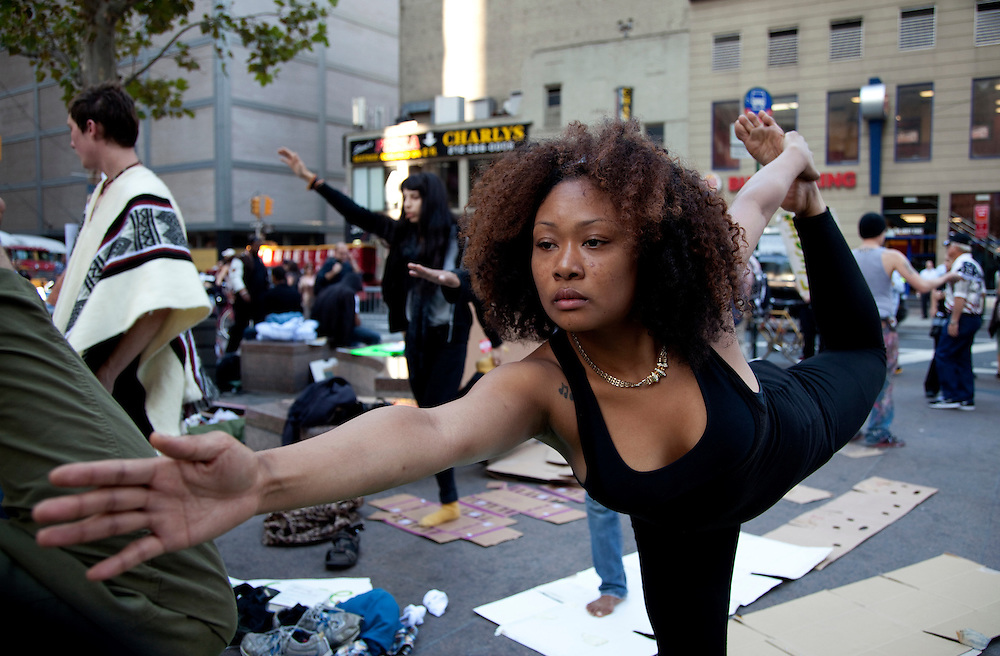 Sade Adoma practices yoga with other demonstrators at Occupy Wall Street in Zuccotti Park, New York City, NY on October 10, 2011.
