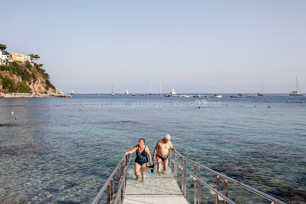 04 August 2017, Capri Italy - A couple of old people in the morning go up from the sea with a catwalk after bath in Marina Grande.