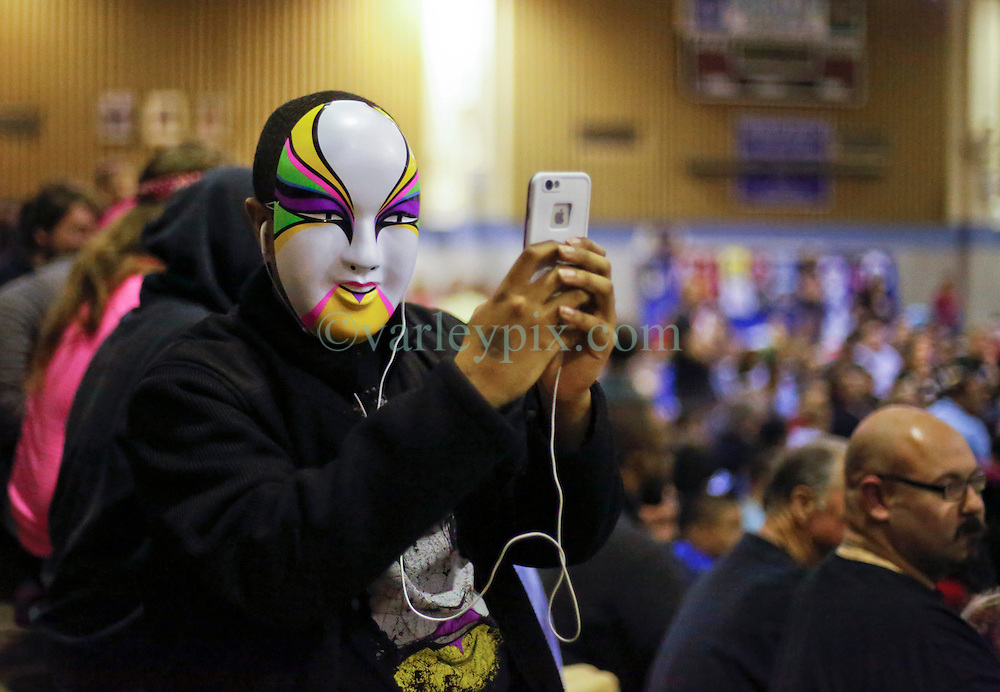 12 March 2016. Metairie, Louisiana.<br /> Wrestling action from Wildkat Sports and Entertainment's 'March into Mayhem' at the Meisler Middle School. A face in the crowd captures the scene on his cell phone.<br /> Photo&copy;; Charlie Varley/varleypix.com
