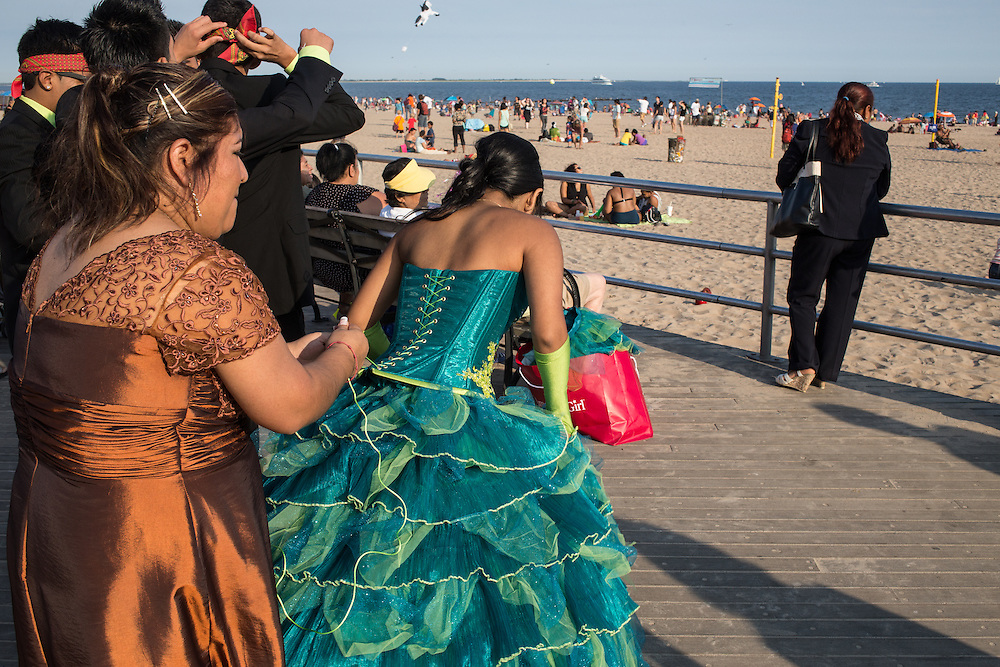A girl with her family and entourage getting laced up for quinceañera photos on the Concey Island boardwalk.