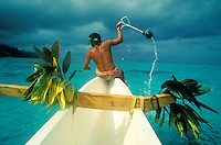 Peches aux Cailloux, fishing with rocks, in Moorea, an island in French Polynesia<br /> <br /> men in boats in a circle smash rocks into the water chasing the fish toward nets near the shore<br /> <br /> Photo by Owen Franken
