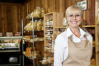 Portrait of a happy senior female employee in grocery store