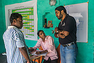 Technoserve Market Linkage Manager Rajiv Shinde (in dark blue t-shirt) supervises as Jeevika Field Associate Raju Kumar (in pink shirt) keeps purchasing records and issues receipts to producer group farmers selling vegetables to the collection centre in Machahi village, Muzaffarpur, Bihar, India on October 27th, 2016. Non-profit organisation Technoserve works with women vegetable farmers in Muzaffarpur, providing technical support in forward linkage, streamlining their business models and linking them directly to an international market through Electronic Trading Platforms. Photograph by Suzanne Lee for Technoserve