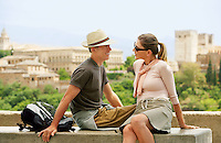 Tourist Couple Relaxing on Wall Granada Spain side view