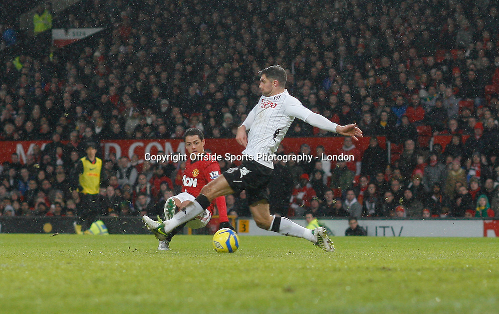26 January 2013 FA Cup Manchester United v Fulham.<br /> Javier Hernandez shoots and the ball deflects off Aaron Hughes for the fourth United Goal.<br /> Photo: Mark Leech.