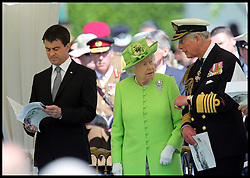 Image ©Licensed to i-Images Picture Agency. 06/06/2014. Bayeux, France.  <br /> In the frame - (L-R) French Interior Minister Manuel Valls, The Queen and The Prince of Wales.<br /> The Queen and The Duke of Edinburgh accompanied by French Interior Minister Manuel Valls, The Prince of Wales and The Duchess of Cornwall attend a service of Remembrance at the Commonwealth War Graves Cemetery in Bayeux, Normandy, France, on the 70th anniversary of D-Day.  Picture by Stephen Lock  / i-Images