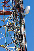 Riggers working on television broadcast tower installing radio system on Mount Stuart, Townsville, Queensland, Australia